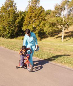 אם מלמדת את בנה לרכב על אופניים