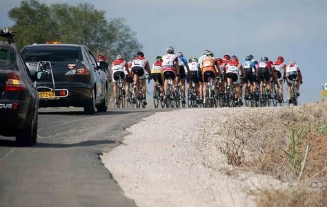 מרוץ סיום העונה באופניים רוכבים עם מכוניות המאמנים מאחור